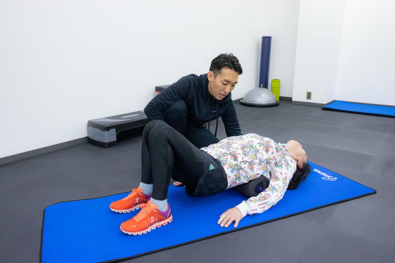 腰痛の女性をリハビリする理学療法士